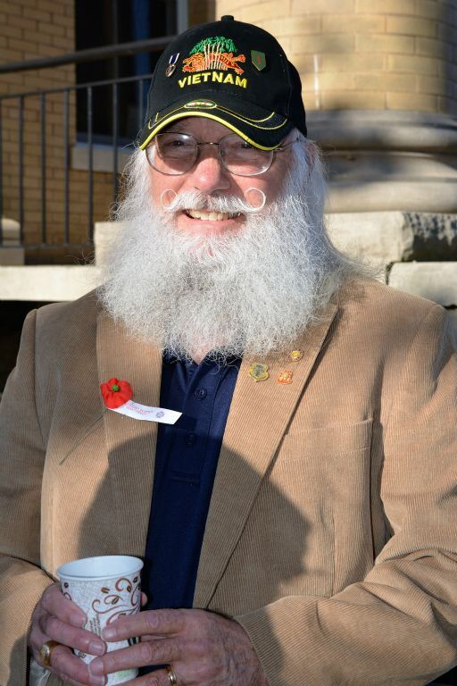 Man wears khaki colored corduroy jacket and Vietnam hat, smiles into camera holding coffee cup